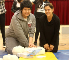 Student Hayden Williamson learning CPR and AED longside Tausha Esquega, representing Hydro One